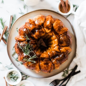 A birds eye view of easy monkey bread on a grey plate. It is surrounded by cinnamon sticks, rosemary, and glasses of milk.