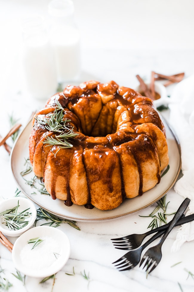 a 3/4 view of easy monkey bread recipe on a grey plate. It is garnished with rosemary and there are glasses of milk in the background.