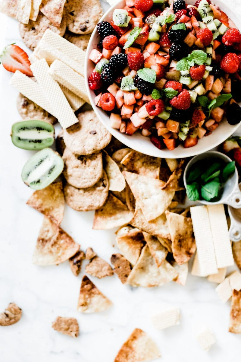 Fruit salsa in a white bowl. There are cookies, chips, and vanilla wafer cookies surrounding the bowl.
