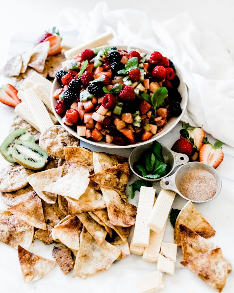 A 3/4 vies of fruit salsa on a marble board. There are cinnamon sugar chips and cookies surrounding the bowl as well as a small bowl of cinnamon sugar and small bowl of mint.