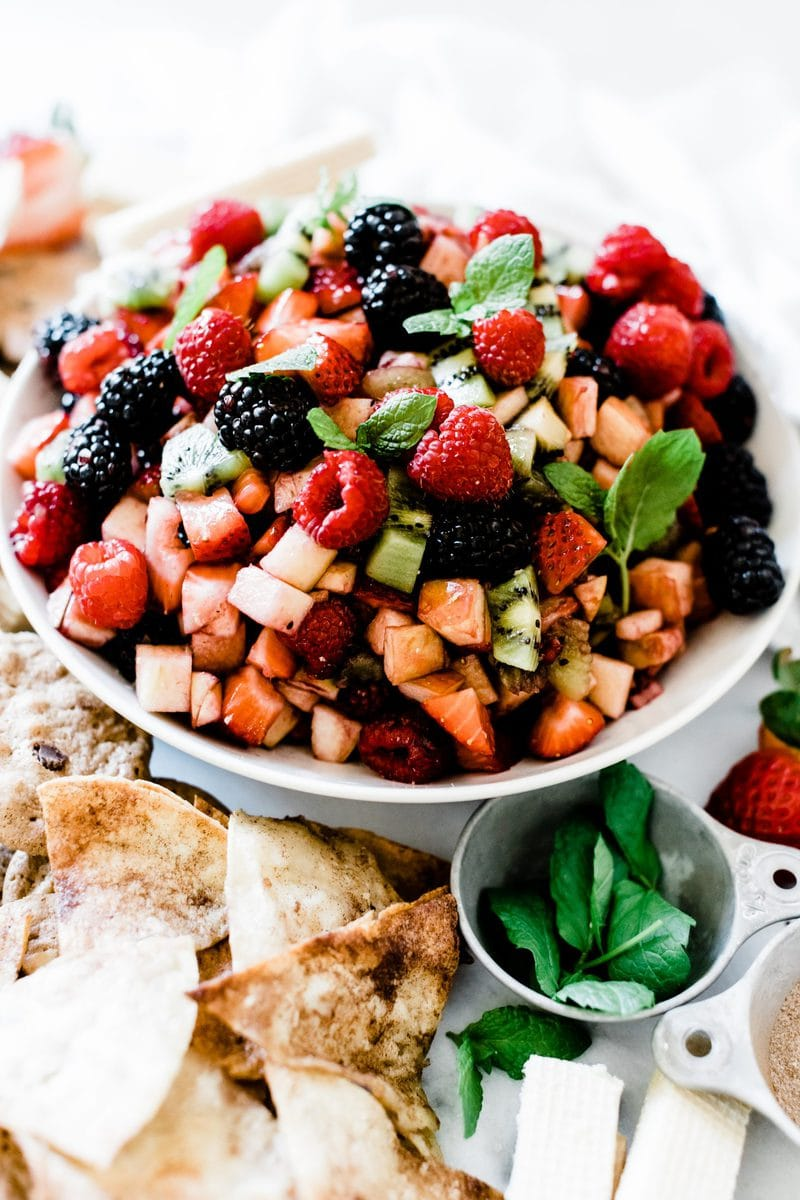 A 3/4 angle close up of fruit salsa in a white bowl. There is mint garnishing the salsa.
