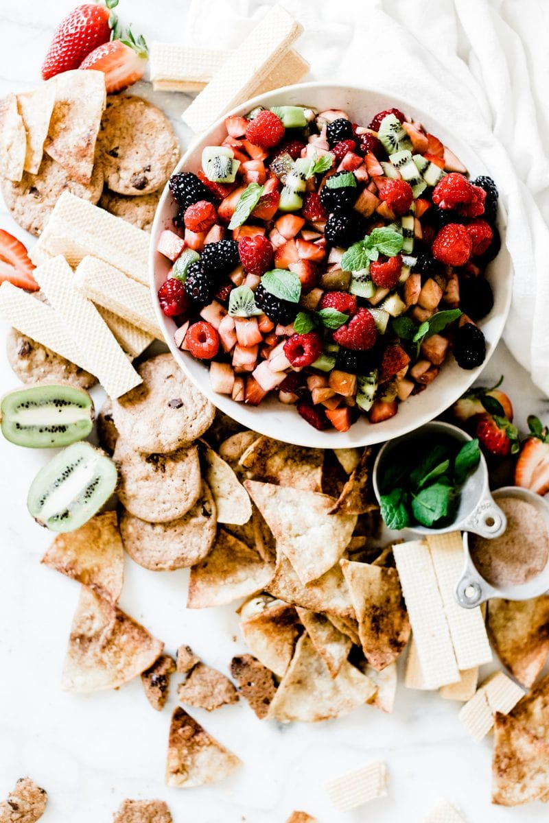 Fruit salsa in a white bowl on a marble board. The bowl is surrounded by cookies and cinnamon chips