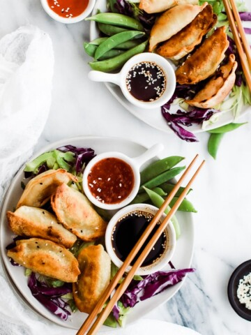 potstickers on a plate with dipping sauces