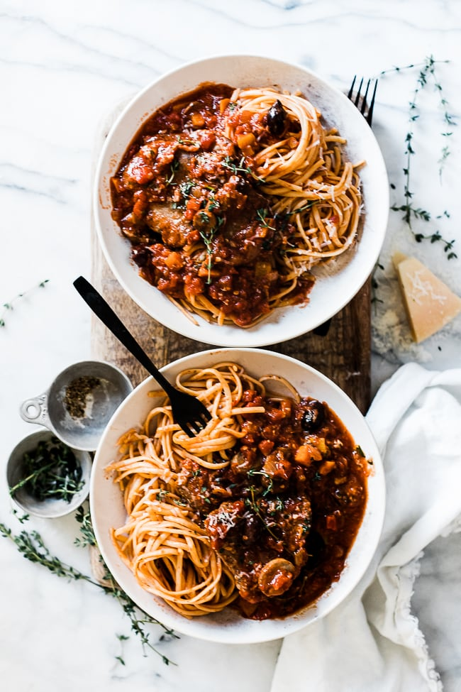 Two white bowls filled with easy lamb cacciatore. They are garnished with thyme.