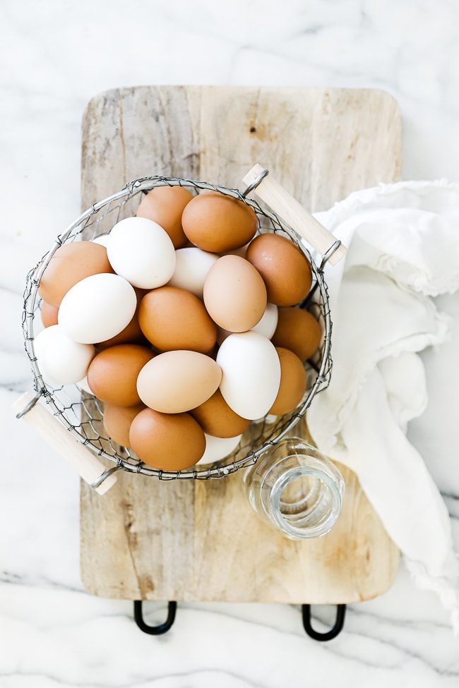 A basket of eggs and a cup of water on a wooden tray,