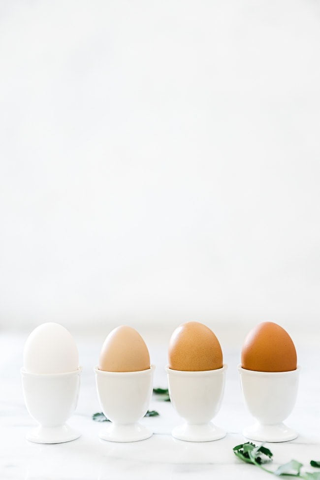 Hard boiled eggs in egg cups. There are 4 lined up - a white egg, a light tan egg, a tan egg, and a dark tan egg.
