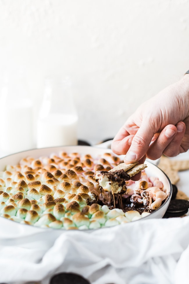 S'mores dip recipe being dipped into with graham crackers.