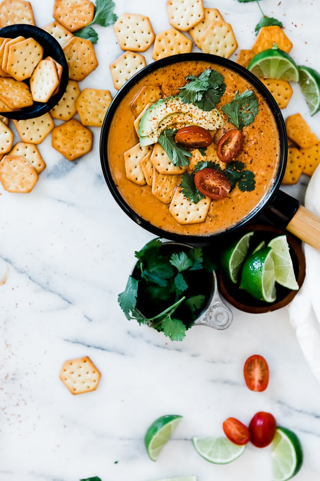 One bowl of Chili's enchilada soup surround's did by cilantro, limes, and crackers.