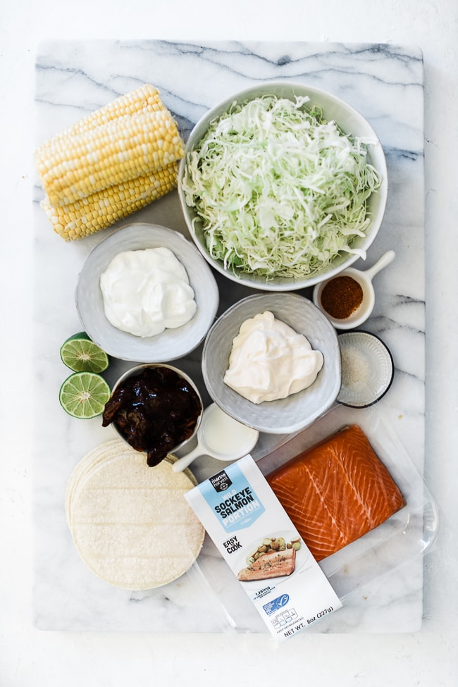 Corn, cabbage, sour cream. mayo, chipotle peppers, limes, salmon, and corn tortillas on a marble board.