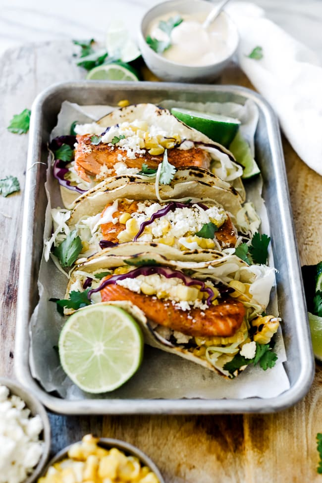 A 3/4 view of blackened salmon tacos on a metal baking tray.