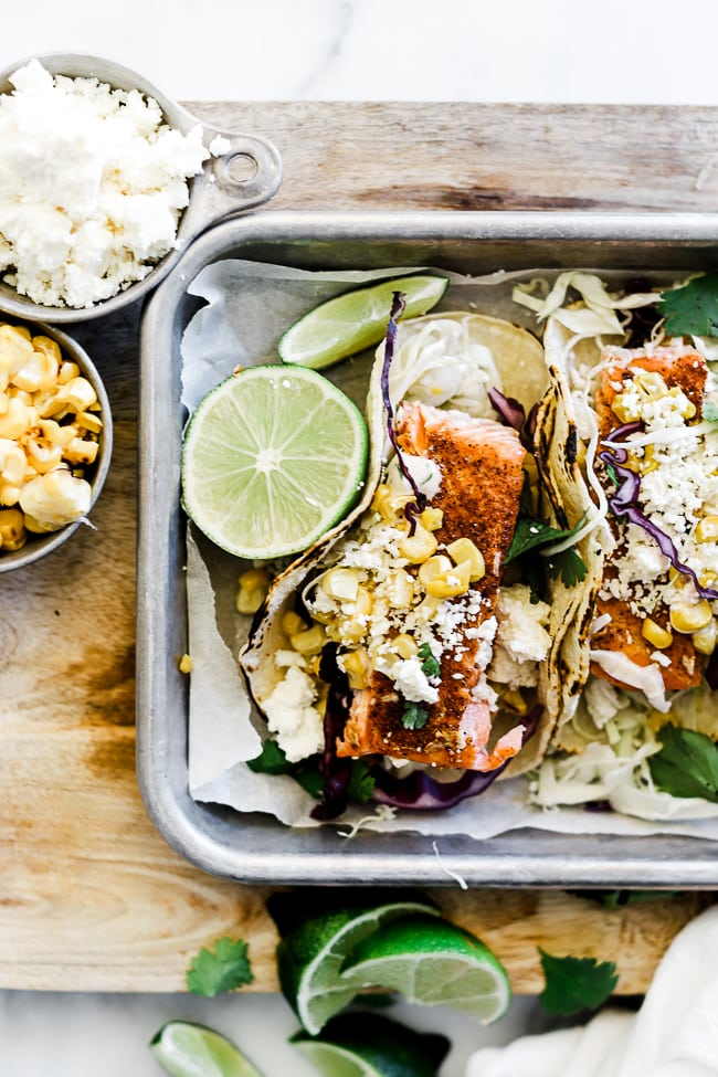 A close up of blacked fish tacos on a metal baking tray.