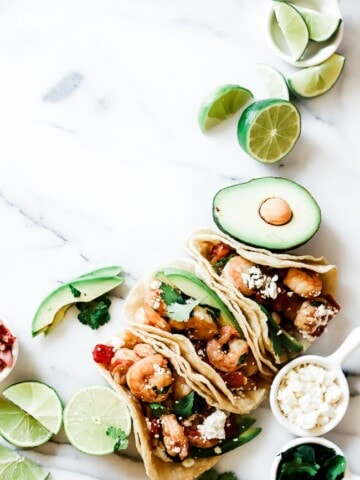 An overhead shop of shrimp tacos on a marble countertop. There are lime slices and avocado surrounding.