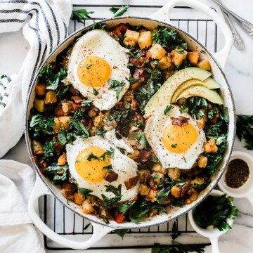 Potato hash recipe in a white braiser. It is set atop a wire cooling rack and topped with sunny side eggs.
