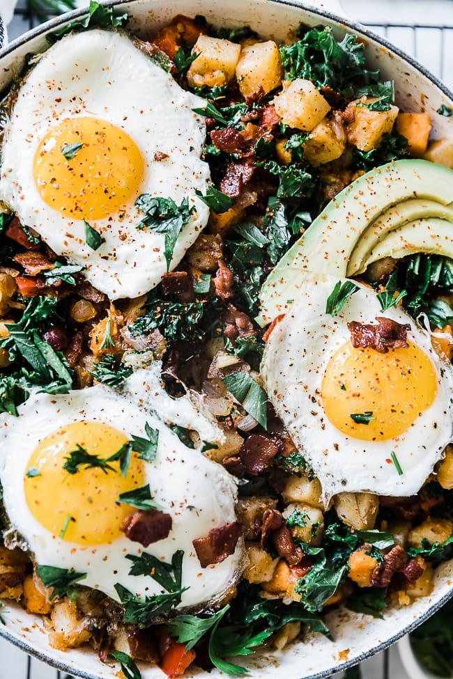 A close up of eggs atop a potato hash.