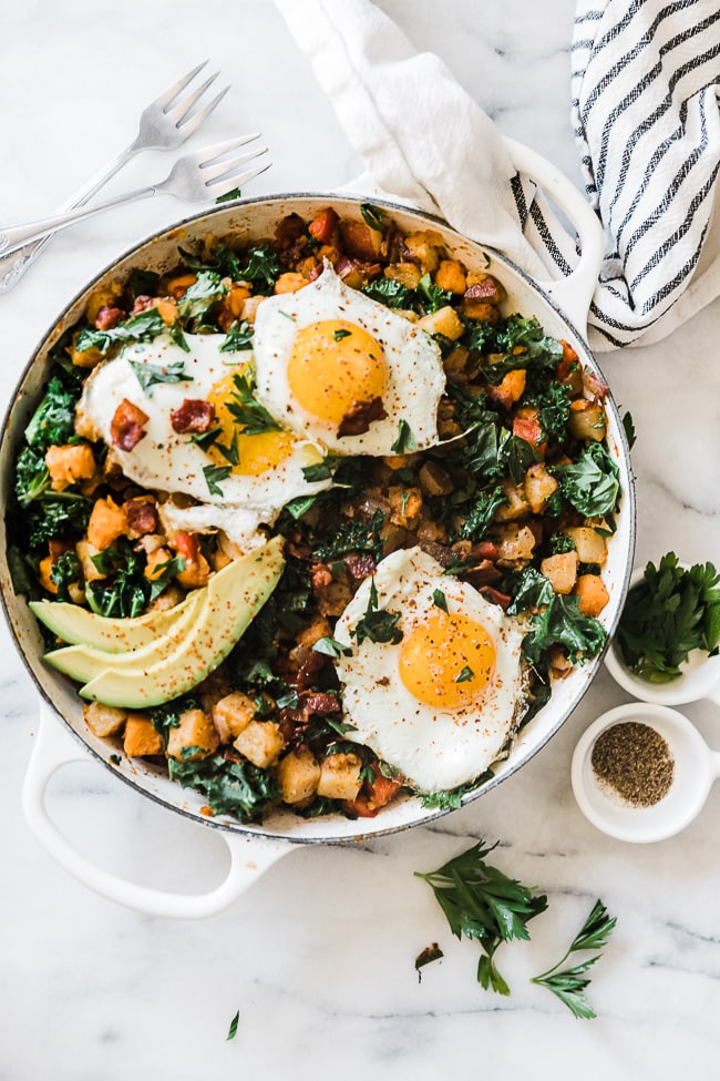 Three sunny side up eggs atop a potato hash.