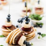 chocolate banana pancake skewers on a marble board. There are blueberries and mint in the background. One skewer is turned on its side.