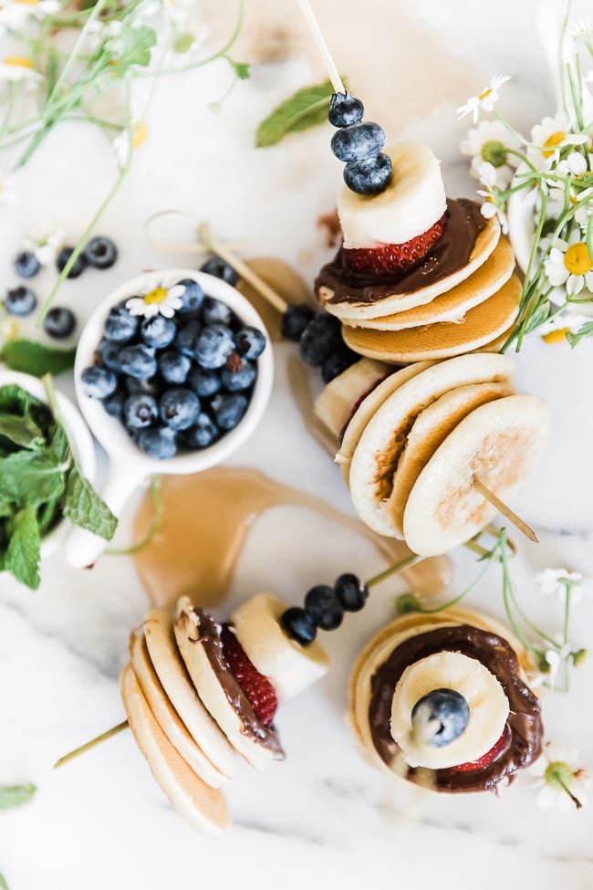 Pancake skewers laid on a marble board. There is a bowl of blueberries to the side and flowers scattered around.