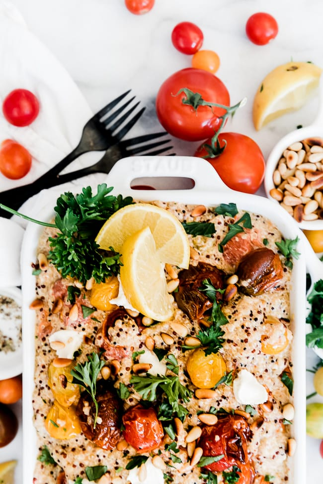 Lemon quinoa with roasted tomatoes in a white casserole dish. It is garnished with lemons and parsley.