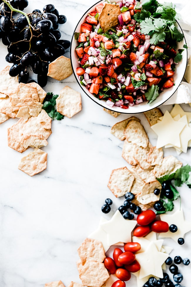 strawberry salsa in the corner of a marble tray surrounded by crackers and cheese.