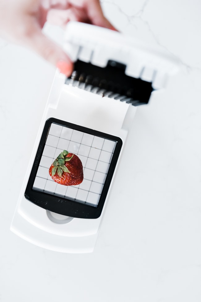 An onion chopper with a strawberry on it.