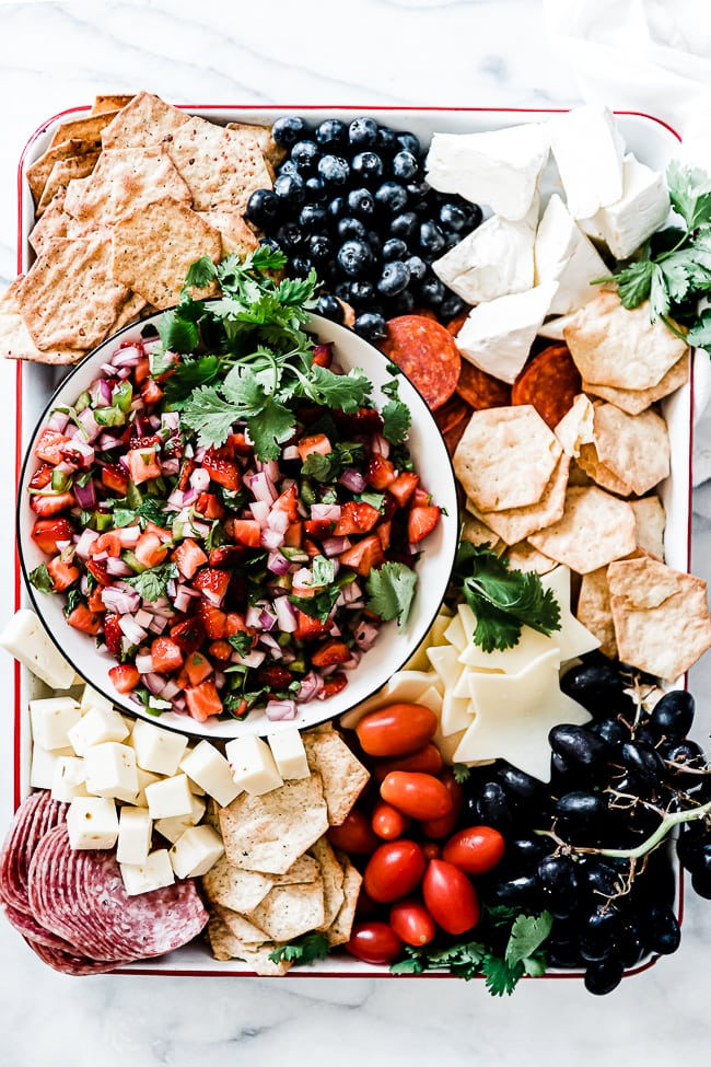 Strawberry salsa on a white tray surrounded by cheese and crackers.