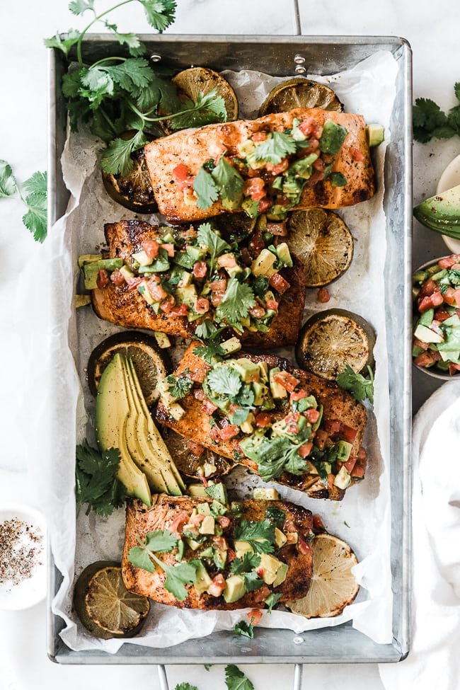 Avocado salmon on a metal tray. Salmon is topped with avocado relish and is surrounded by grilled lime.