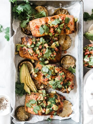 Avocado salmon in a metal tray topped with avocado relish.