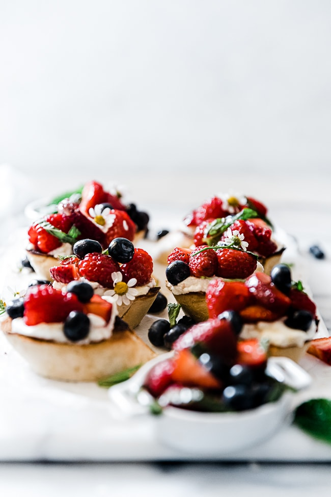 A 3/4 shot of berry bruschetta on a marble tray. The baguette slices are toasted and topped with ricotta and berries.