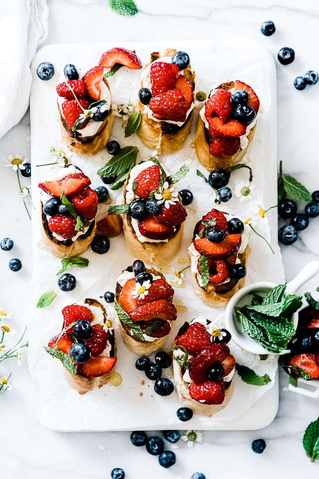 Berry and ricotta bruschetta on a. marble tray.
