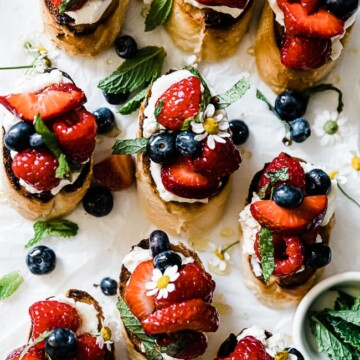 ricotta bruschetta laid on a marble tray. They are garnished with berries and mint.