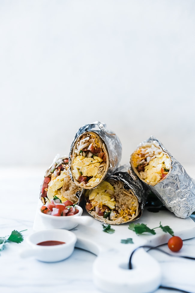 4 burritos wrapped in foil. They are stacked on top of one another.