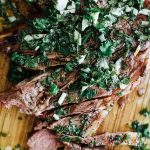 grilled lamb chop with chimichurri cut on wooden cutting board
