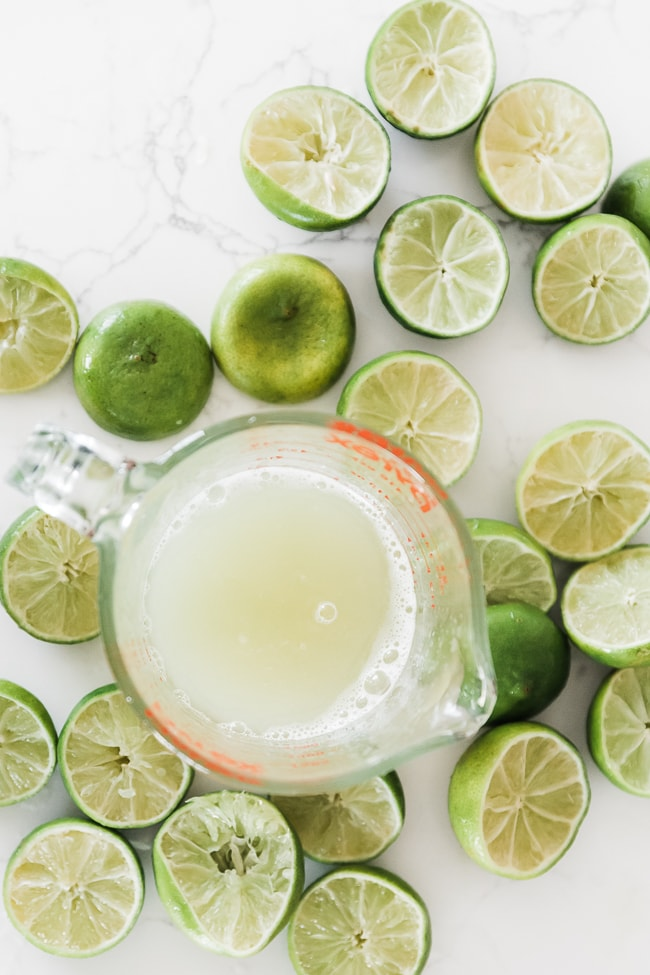 Fresh lime juice in a measuring cup.