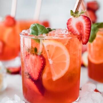 glass of red strawberry basil lemonade with lemons and strawberries as garnish