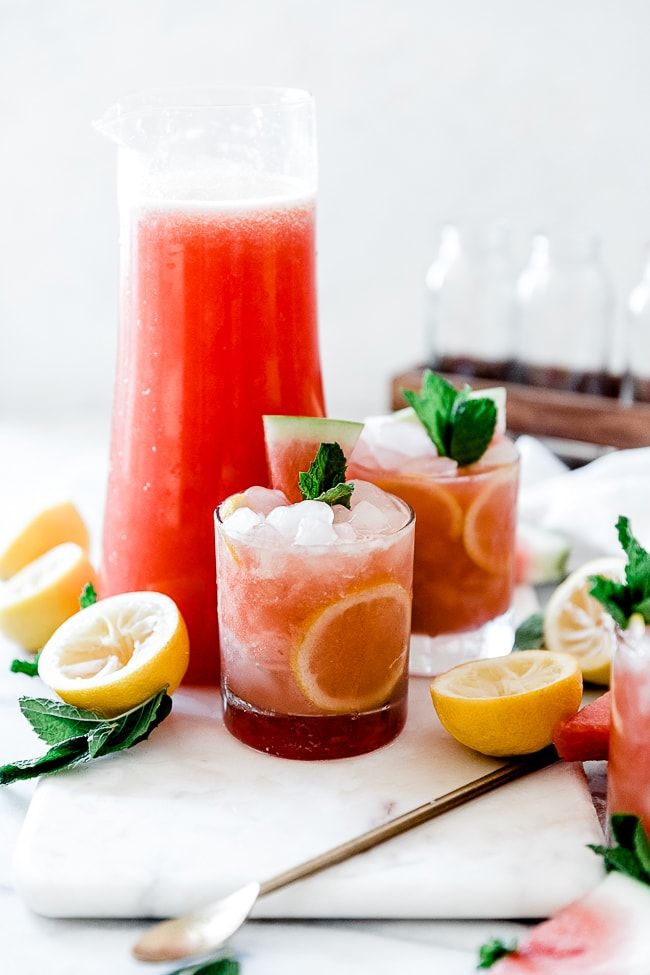 Watermelon lemonade in a tall pitcher with glasses set next to it.