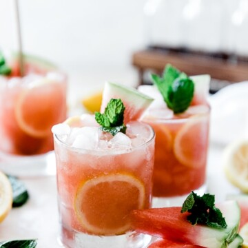 Watermelon lemonade in short glasses, garnished with mint and watermelon.