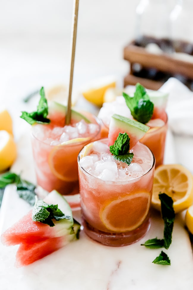 Three glasses of watermelon lemonade set together on a marble tray, surrounded by watermelon slices and lemons.