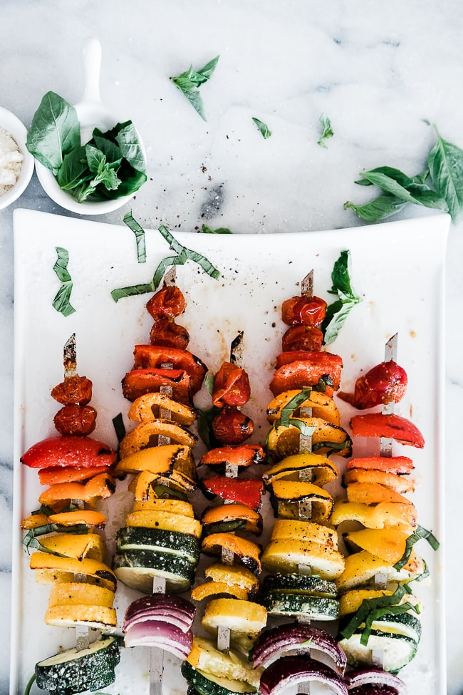 Grilled vegetable skewers placed on a white rectangle tray. There is a bowl of basil and parmesan to the side.