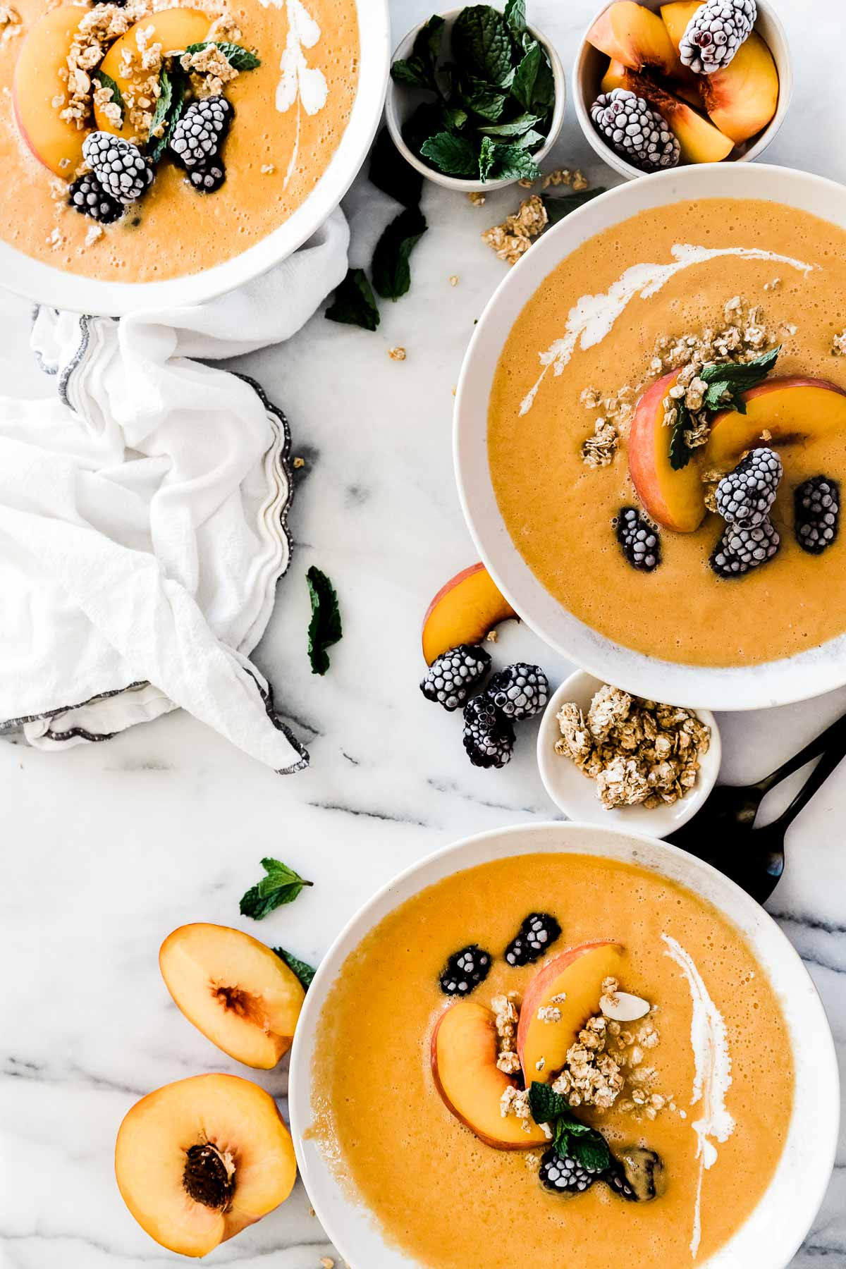 Three white bowls filled with peach chilled soup. The soup is garnished with peaches, berries, and mint.