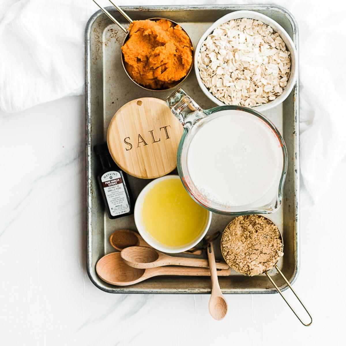 Ingredients for pumpkin oatmeal on a metal tray - oats, pumpkin, almond milk, sugar.