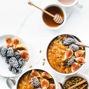 Two bowls of pumpkin oatmeal. The oats are garnished with berries and gas, and there are small bowls of berries and honey to the side.