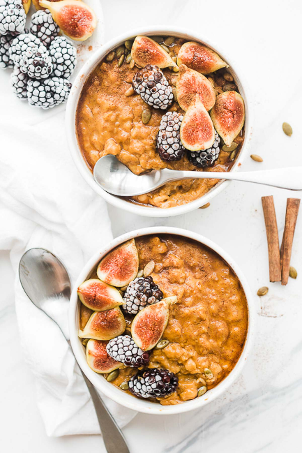 Two bowls of pumpkin oatmeal in white bowls.  There are silver spoons and cinnamon sticks to the side.