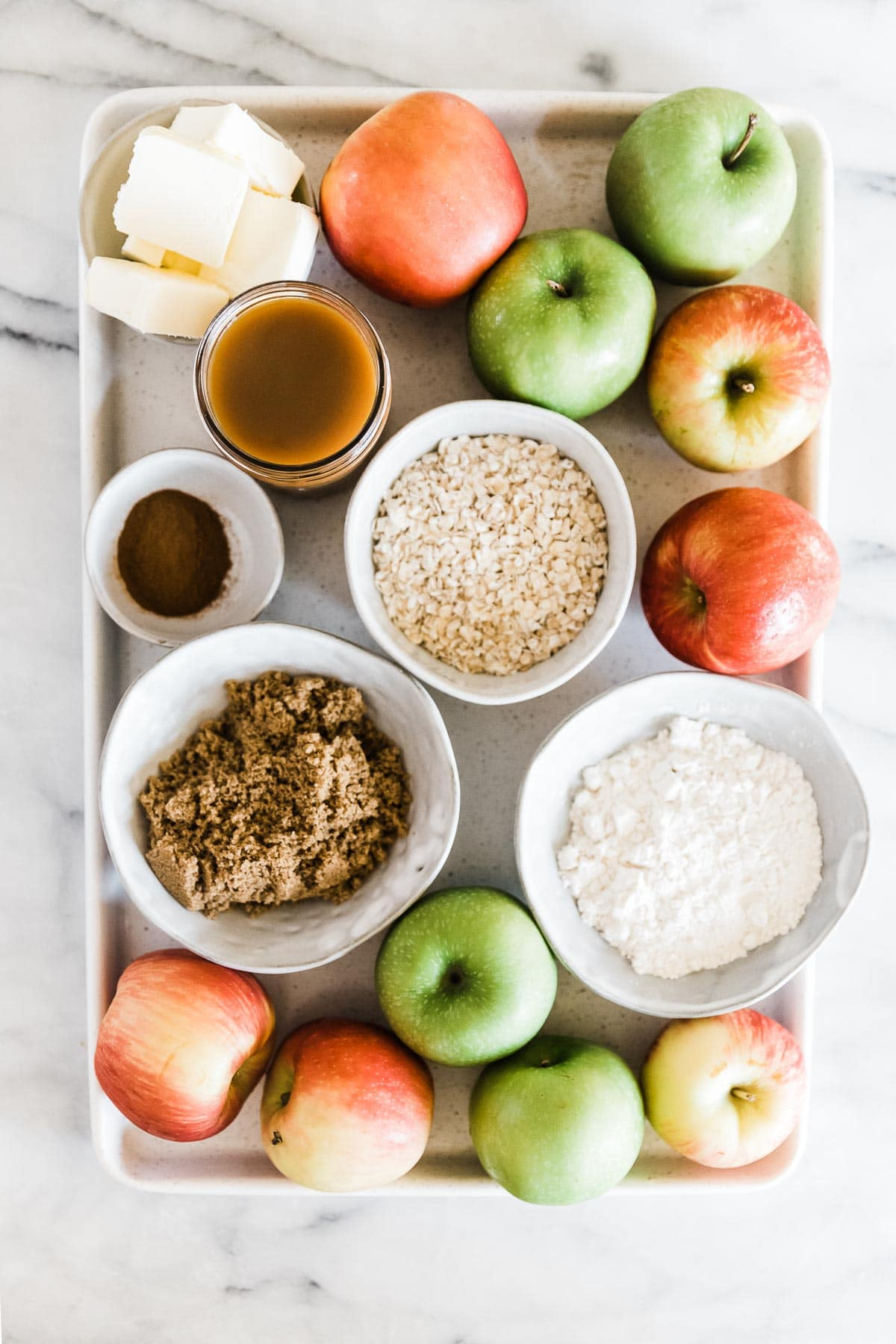 Apples, oats, flour, brown sugar, cinnamon, and caramel on a white baking tray.