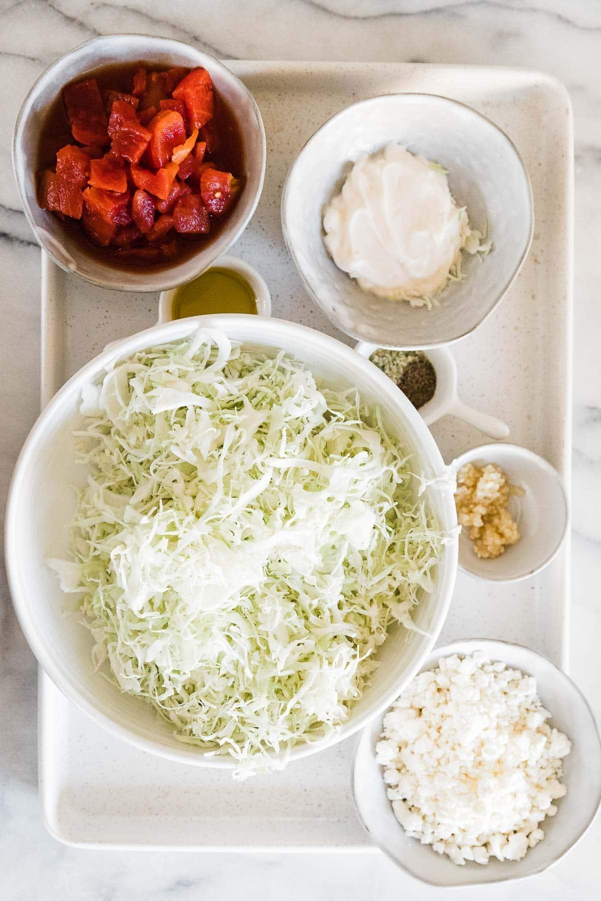 Cabbage, mayo, roasted tomatoes, and garlic on a white baking sheet.