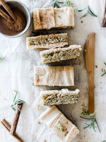 Six zucchini bars lined up next to a wooden knife. There is a bowl of cinnamon to the side.