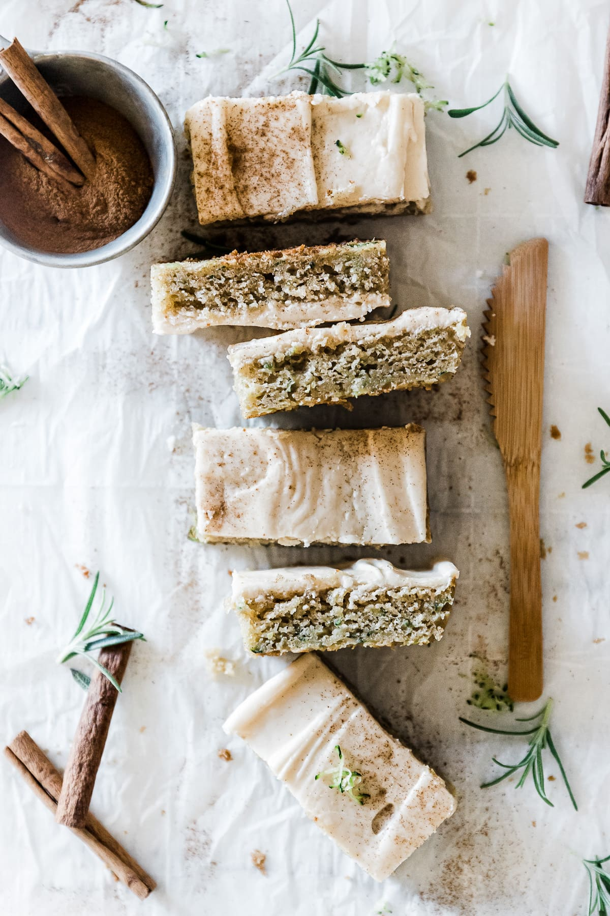 Siz zucchini bars lined up next to a wooden knife. There is bowl of cinnamon to the side.