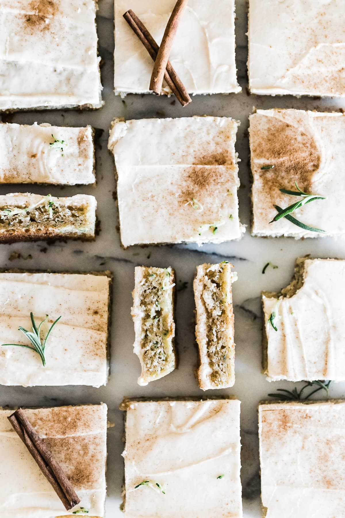 Zucchini bars cut into squares and lined up on a marble counter. They are garnished with cinnamon.