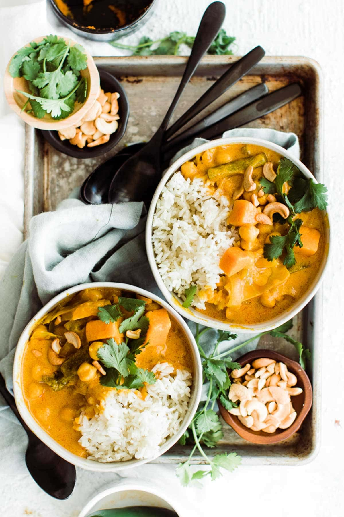 two bowls of pumpkin curry on a grey tray with black spoons