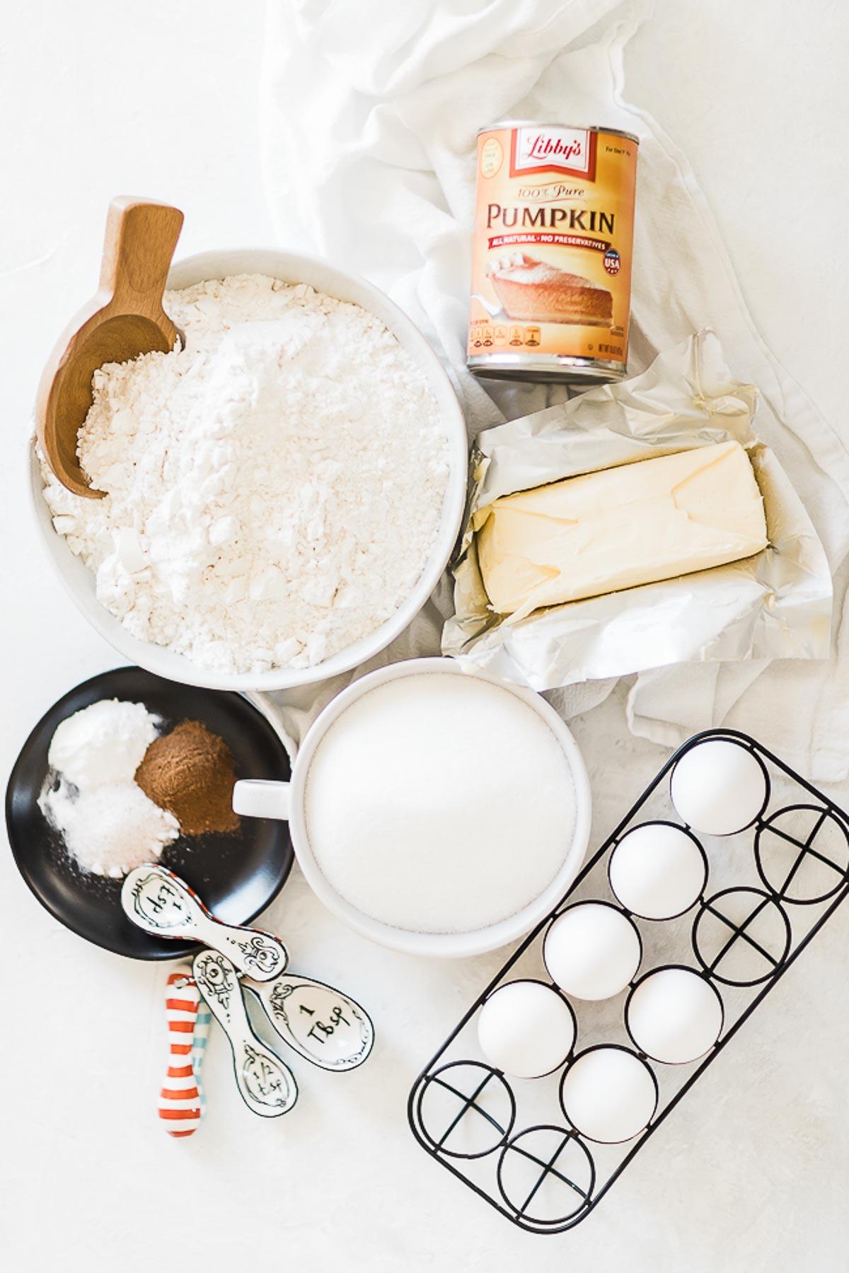 Flour, pumpkin, shortening, eggs, sugar and spices on a white counter.