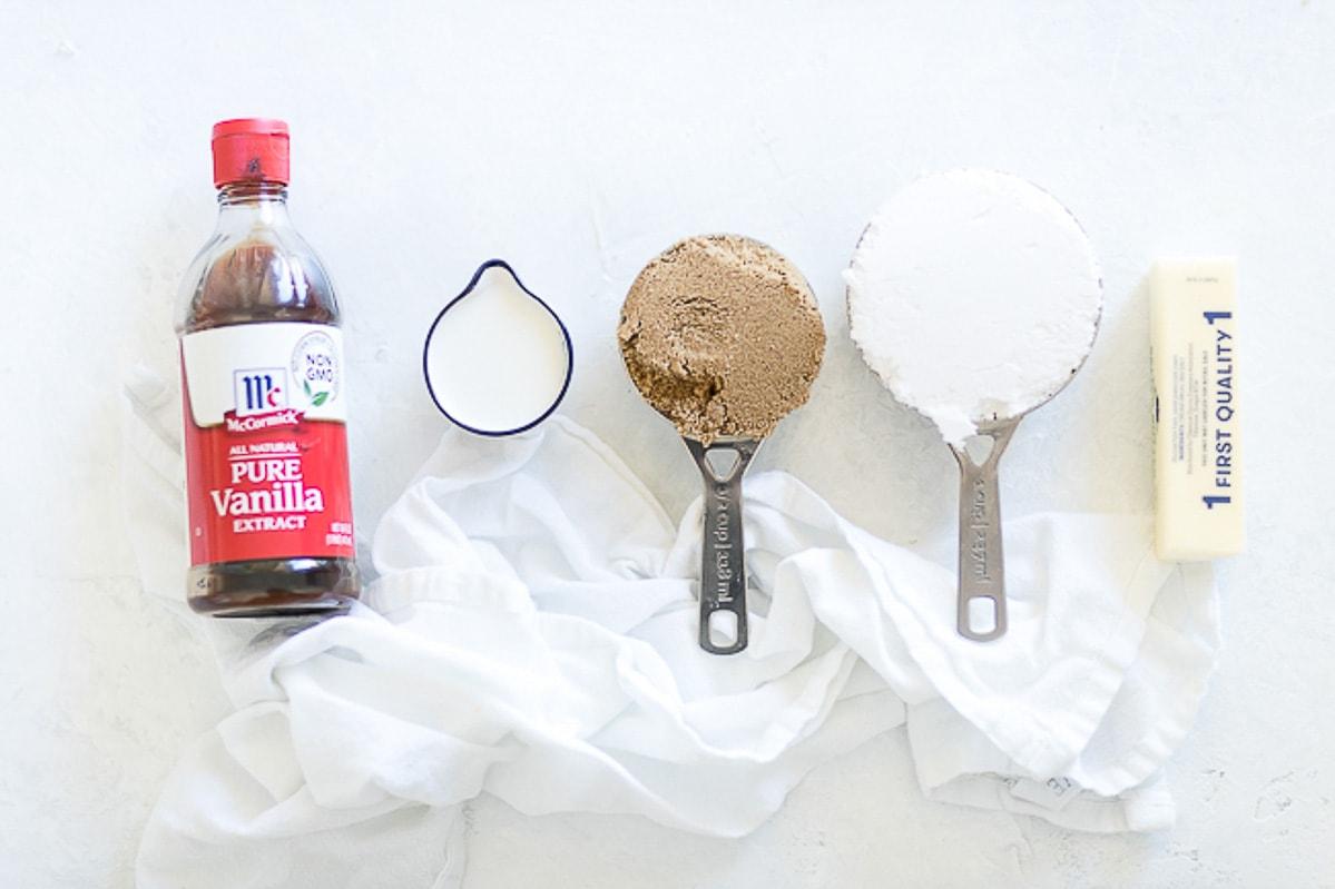 Vanilla, brown sugar, milk, powdered sugar and butter on a white counter.